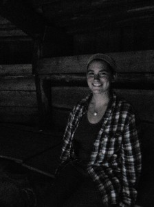 Emily inside the reconstructed pithouse. She is sitting on the bench and behind her are the cubbies.